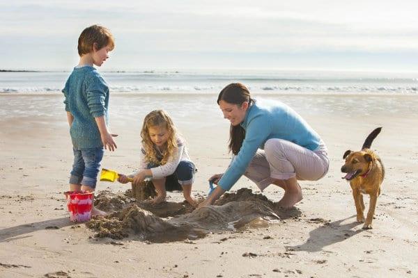 Family enjoying beach with dog Long Beach CA Real Estate